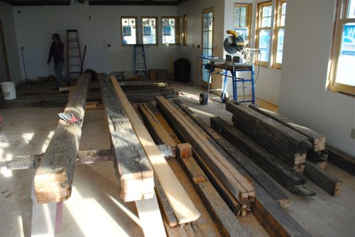 Old beams lying in the living room. The workers are preparing to put them up on the ceiling.