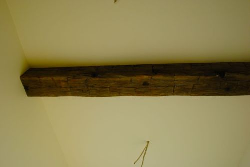 Close up of old beam in hallway showing marks of age and the hand tools that crafted the beams one hundred years ago.