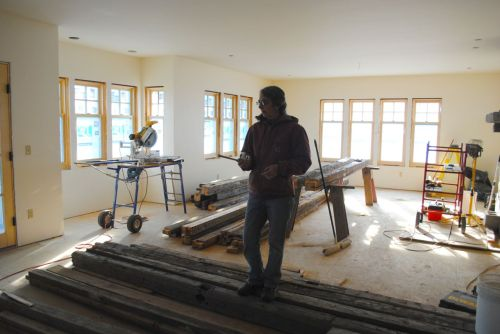 Laurie Southworth of Southslope Woodworks stands atop a pile of old beams in the living room.