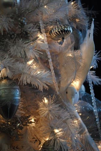 A bird of peace peeks around the Christmas tree bringing good cheer to all in the dining room.
