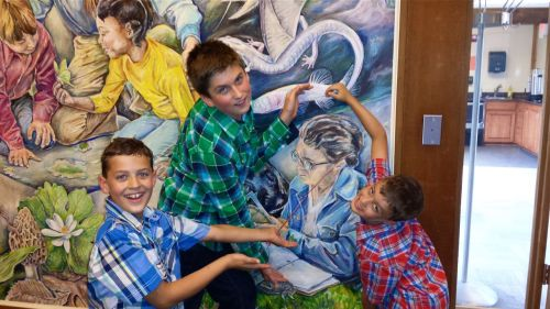 Mural designed and painted by Charles Schwartz.  Three great-grandsons (Braden, Kaeden, and Avery) surround an image of Libby working on her journal.