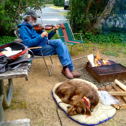 Bullard's Beach State Park Oregon Coast. Gypsy on her sleeping bag dreaming about new ways to open doors while Bruce plays fiddle tunes in front of the fire.