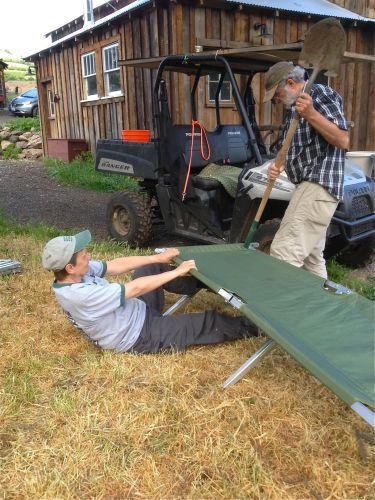 Heidi and Bruce work to stretch the canvas over our military cots for the great camp out that did not happen.